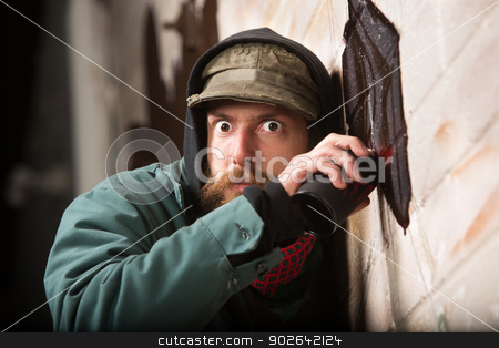 Tense Man Tagging a Wall stock photo, Tense European man by wall using spray paint by Scott Griessel