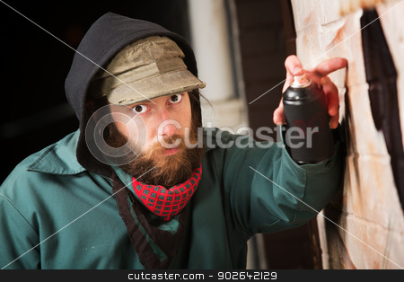 Hooded Man Tagging a Wall stock photo, Serious man with hood spray painting a wall by Scott Griessel
