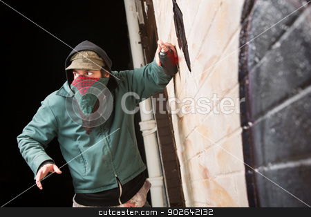 Worried Gang Member Spray Painting stock photo, Scared disguised criminal defacing a wall outdoors by Scott Griessel