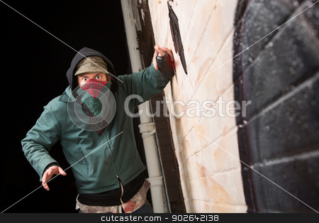 Scared Gangster with Spray Paint stock photo, Scared gang member with spray pain can near wall by Scott Griessel