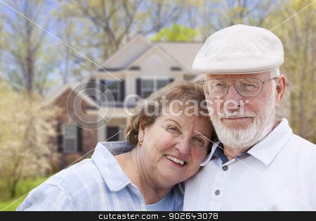 Happy Senior Couple in Front of House stock photo, Attractive Happy Senior Couple in Front Yard of House. by Andy Dean