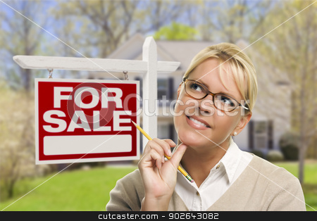 Young Woman in Front of Sold Sign and House stock photo, Attractive Young Adult Woman with Pencil in Front of For Sale Real Estate Sign and House. by Andy Dean
