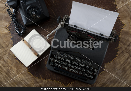 Vintage typewriter, pen and paper on an antique table stock photo, Vintage antique typewriter ready to start typing on a blank piece of paper. Also on the table are an antique rotary telephone, note pad and pen. by Tom Robinson