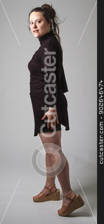 Turning around stock photo, Woman wearing a black dress with wispy flowing hair, looking over her shoulder by Yann Poirier