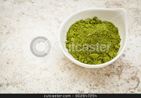 moringa leaf powder stock photo, moringa leaf powder in a small bowl against a ceramic tile background by Marek Uliasz