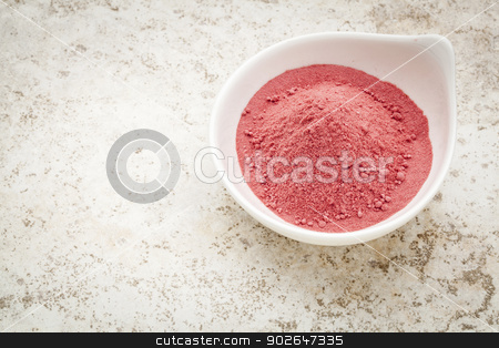 Organic yumberry powder stock photo, Organic yumberry powder in a small bowl against a ceramic tile background by Marek Uliasz