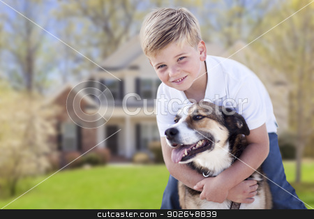 Young Boy and His Dog in Front of House stock photo, Happy Young Boy and His Dog in Front Yard of Their House. by Andy Dean