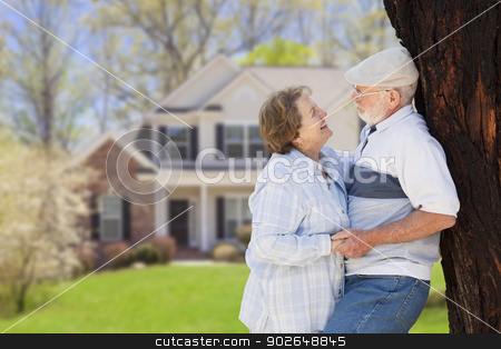 Happy Senior Couple in Front Yard of House stock photo, Happy Senior Couple in the Front Yard of Their House. by Andy Dean
