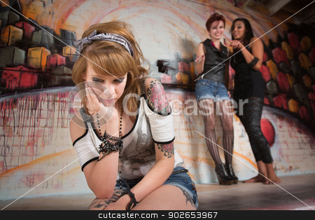 Sad Girl Being Bullied stock photo, Sad European young woman being teased by group of teenagers by Scott Griessel