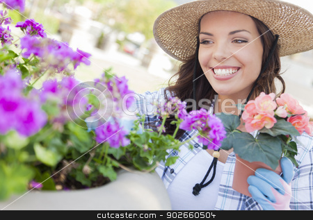 Young Adult Woman Wearing Hat Gardening Outdoors stock photo, Attractive Happy Young Adult Woman Wearing Hat Gardening Outdoors. by Andy Dean