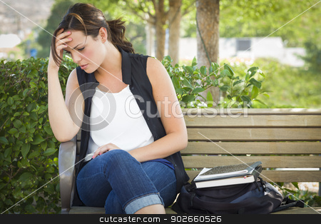 Upset Young Woman Sitting Alone on Bench Next to Books stock photo, Upset Young Woman Sitting Alone with Her Head in Her Hands on Bench Next to Books and Backpack. by Andy Dean