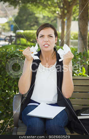 Upset Young Woman with Pencil and Crumpled Paper in Hands stock photo, Frustrated and Upset Young Woman with Pencil and Crumpled Paper in Her Hands Sitting on Bench Outside. by Andy Dean