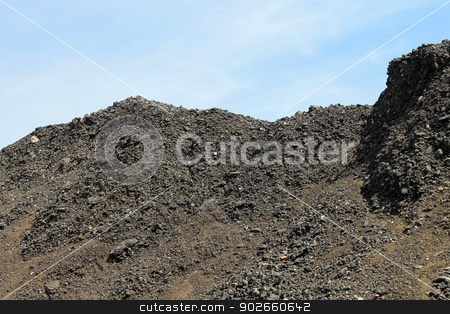 Pile of coal stock photo, Side view of pile of coal with blue sky background. by Martin Crowdy
