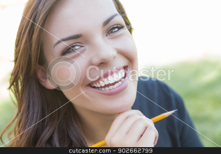 Portrait of Pretty Young Female Student with Pencil on Campus stock photo, Portrait of Pretty Young Female Student with Pencil on Campus Lawn. by Andy Dean