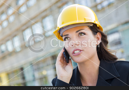 Young Female Contractor Wearing Hard Hat on Site Using Phone stock photo, Young Professional Female Contractor Wearing Hard Hat at Contruction Site Using Cell Phone. by Andy Dean