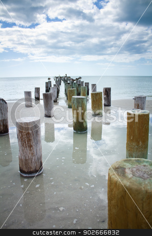 Old wood pier stumps at the beach stock photo, Old, run down wooden pier stumps with pelicans sitting on them on a partly cloudy day.  by Amanda Webb