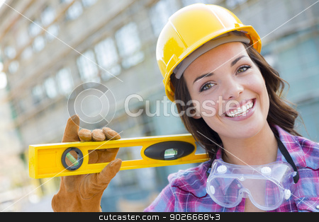 Young Attractive Female Construction Worker Wearing Hard Hat and stock photo, Portrait of Young Attractive Female Construction Worker with Level Wearing Gloves, Hard Hat and Protective Goggles at Construction Site. by Andy Dean
