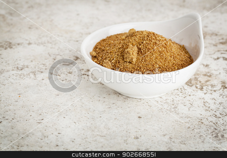 coconut palm sugar stock photo, small ceramic bowl of unrefined coconut palm sugar against a ceramic tile background with a copy space by Marek Uliasz