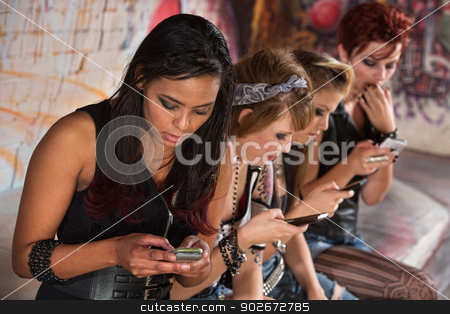 Mixed Group Texting stock photo, Mixed group of girls looking down at their phones by Scott Griessel