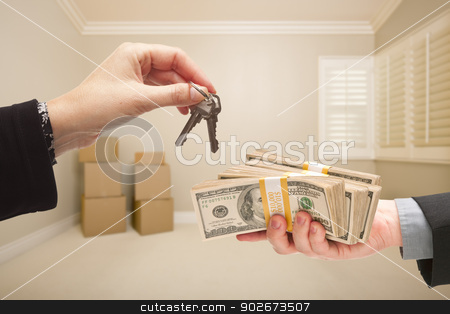Handing Over Cash For House Keys stock photo, Man and Woman Handing Over Cash For House Keys Inside Empty Tan Room with Boxes. by Andy Dean