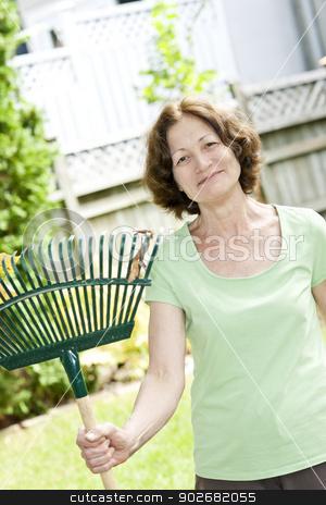 Senior woman holding rake stock photo, Senior woman smiling holding rake for yard work outside by Elena Elisseeva