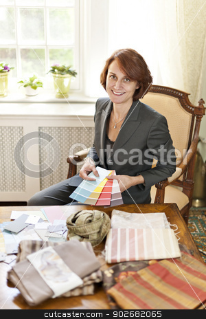 Female interior designer stock photo, Female interior designer with color samples sitting at desk by Elena Elisseeva