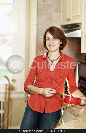 Smiling woman in kitchen at home stock photo, Smiling mature woman enjoying cooking in kitchen at home by Elena Elisseeva
