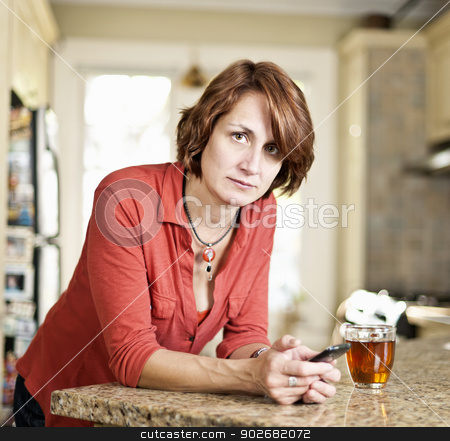 Concerned mature woman in kitchen stock photo, Worried mature woman holding mobile phone in kitchen at home by Elena Elisseeva