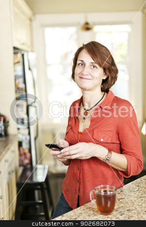 Woman in kitchen with cell phone stock photo, Smiling mature woman using mobile phone in kitchen at home by Elena Elisseeva