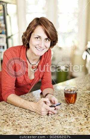 Woman using cell phone at home stock photo, Smiling mature woman using mobile phone in kitchen at home by Elena Elisseeva