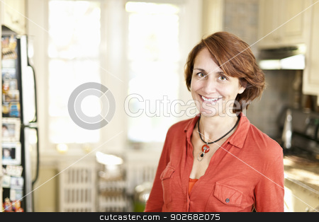 Happy woman in kitchen at home stock photo, Portrait of smiling mature woman in kitchen at home by Elena Elisseeva