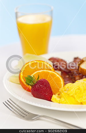 Breakfast plate with fork stock photo, Healthy breakfast of scrambled eggs bacon fruit and orange juice by Elena Elisseeva
