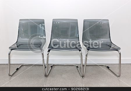 Three plastic chairs against wall stock photo, Three gray transparent plastic and metal chairs in a row by Elena Elisseeva