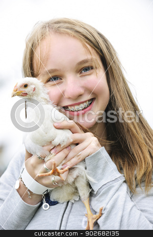Teenage girl holding chicken stock photo, Smiling teenage girl with braces holding young chicken by Elena Elisseeva