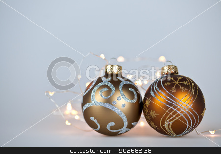 Golden Christmas ornaments stock photo, Two gold Christmas decorations and decorative lights on gray background with copy space by Elena Elisseeva