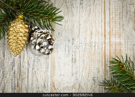 Christmas background with ornaments on branch stock photo, Christmas golden balls and pine cone on spruce branch with wooden background by Elena Elisseeva