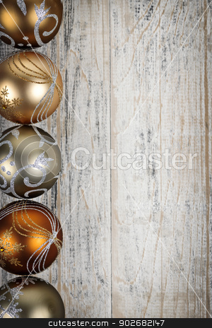 Golden Christmas ornaments border stock photo, Row of golden Christmas balls with festive designs on wooden background by Elena Elisseeva