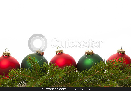Border of green and red Christmas balls stock photo, Row of green and red Christmas ornaments with pine tree branches by Elena Elisseeva