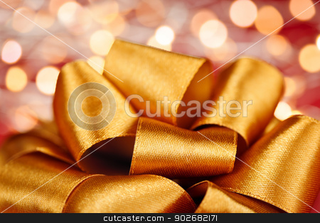 Gold gift bow with festive lights stock photo, Golden ribbon gift bow closeup with festive lights by Elena Elisseeva