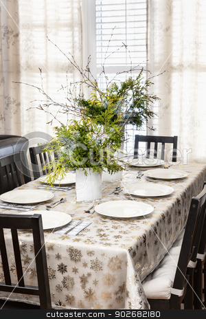 Decorated Christmas dining table stock photo, Dining table decorated for Christmas with eight place settings and evergreen centerpiece by Elena Elisseeva
