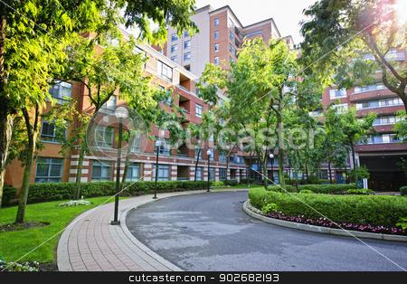 Condo building and driveway stock photo, Circular driveway and sidewalk at brick condominium building by Elena Elisseeva