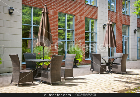 Tables and chairs on outdoor patio stock photo, Patio furniture with umbrellas on stone patio near upscale condo building by Elena Elisseeva