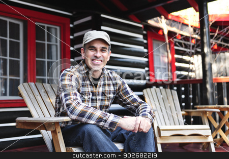 Smiling man relaxing at cottage stock photo, Smiling man sitting on cottage deck in wooden adirondack chair by Elena Elisseeva