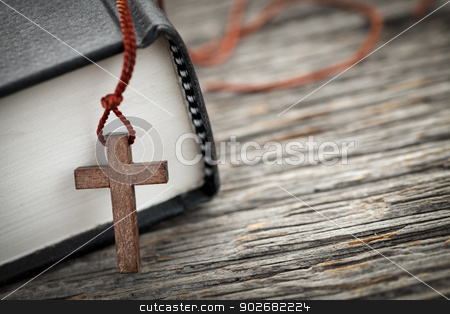 Cross and Bible stock photo, Closeup of wooden Christian cross necklace next to holy Bible by Elena Elisseeva