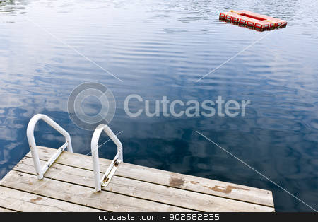 Dock on calm summer lake stock photo, Dock and ladder on calm summer lake with diving platform in Ontario Canada by Elena Elisseeva
