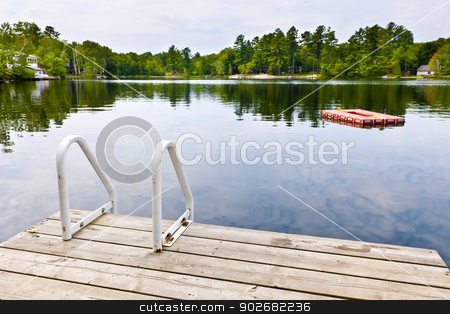 Dock on calm lake in cottage country stock photo, Dock and ladder on summer lake with diving platform in Ontario Canada by Elena Elisseeva
