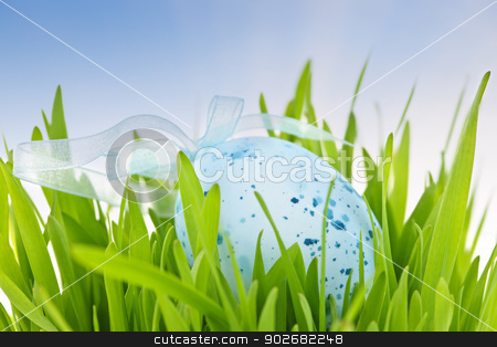 Blue Easter egg in green grass stock photo, Blue speckled easter egg with ribbon in green grass by Elena Elisseeva