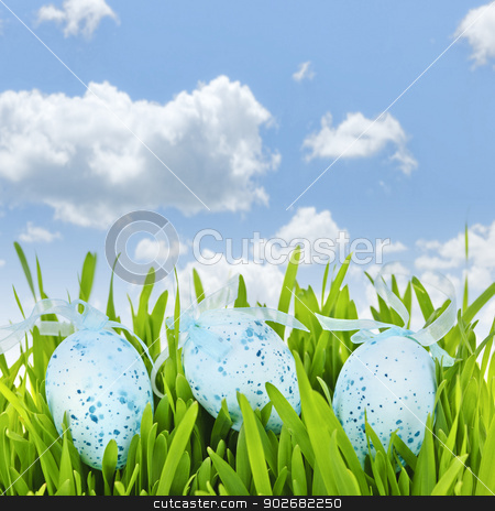 Easter eggs in green grass stock photo, Three blue speckled easter eggs with ribbons in green grass on sky background by Elena Elisseeva