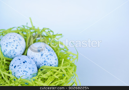 Easter eggs in nest on blue background stock photo, Three blue speckled easter eggs in green paper grass nest with copy space by Elena Elisseeva