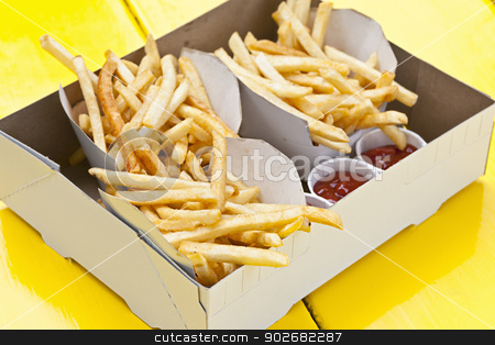 French fries in box stock photo, Portions of french fried potatoes with ketchup in cardboard take-out box by Elena Elisseeva